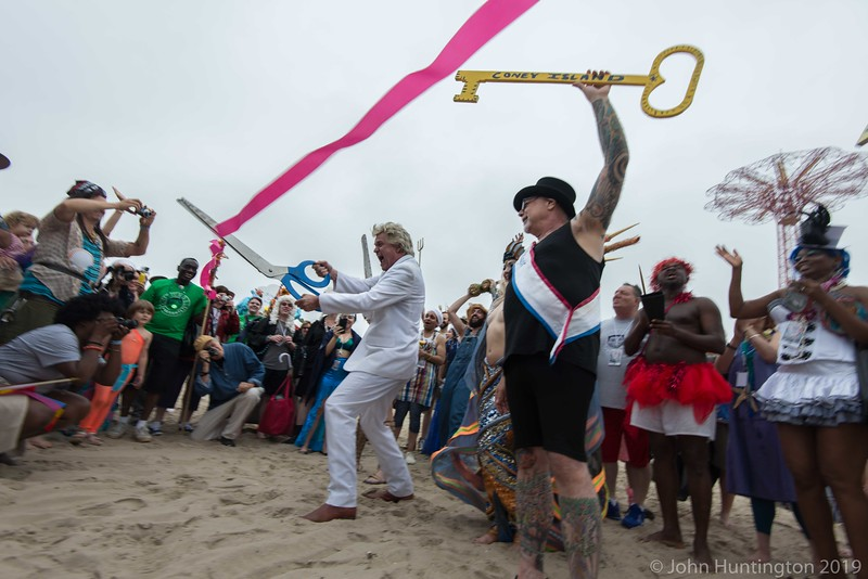 """CONEY ISLAND, BROOKLYN, NY/USA - JUNE 20, 2015: """"Reverend Billy"""" cuts the ribbon representing a season as they march towards the ocean after the annual Mermaid Parade."""