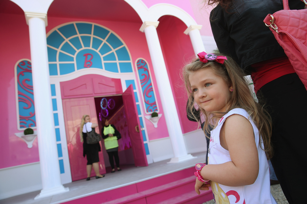 . Selina, 6, waits to enter the Barbie Dreamhouse Experience with her mother on May 16, 2013 in Berlin, Germany. The Barbie Dreamhouse is a life-sized house full of Barbie fashion, furniture and accessories and will be open to the public until August 25 before it moves on to other cities in Europe.  (Photo by Sean Gallup/Getty Images)