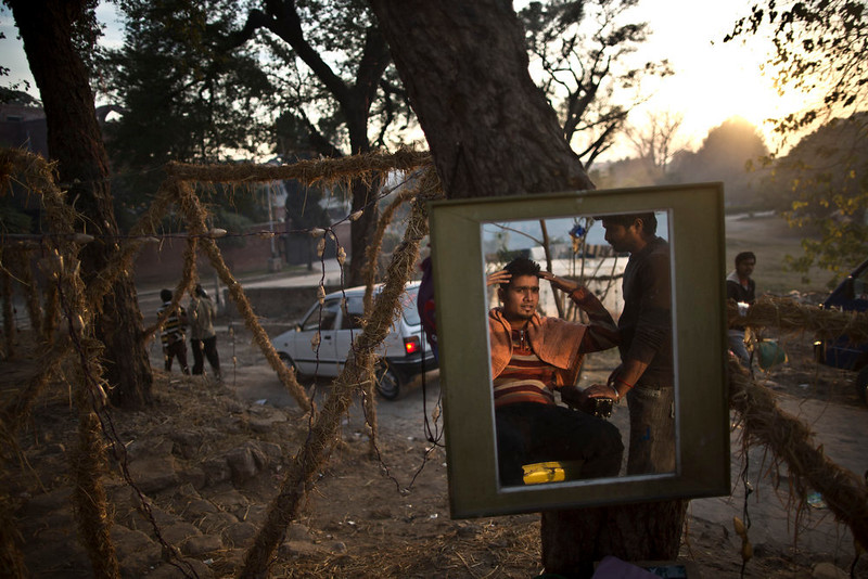 . A Pakistani Christian man gets a haircut at a street barber in preparation for Christmas in a Christian neighborhood in Islamabad, Pakistan, Wednesday, Dec. 24, 2014. (AP Photo/Muhammed Muheisen)