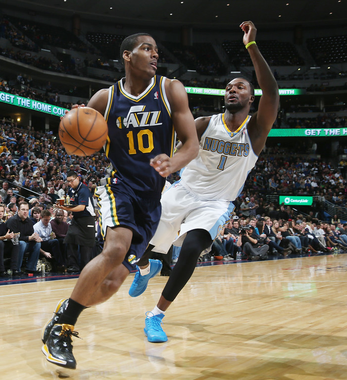 . Utah Jazz guard Alec Burks, front, slips past Denver Nuggets forward Jordan Hamilton for a shot in the fourth quarter of Utah\'s 103-93 victory in an NBA basketball game in Denver on Friday, Dec. 13, 2013. (AP Photo/David Zalubowski)