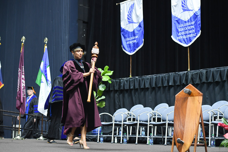 Dr. Corinne Valadez, Associate Professor of Education, Silverman Endowed Professor in Literacy, and recipient of the University Excellence Award in Service, carries the ceremonial mace during opening ceremonies.