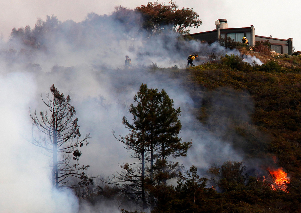 . Firefighters defend a home from a wildland fire in the Pfeiffer Ridge area in Big Sur, Calif. on Monday December 16, 2013. (Photo David Royal/ Monterey County Herald)