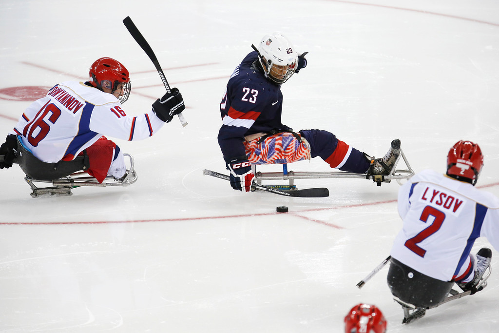 . United States\' Rico Roman, center, in action with Russia\'s Andrey Dvinyaninov, left, and Alekxei Lysov during an ice sledge hockey match between United States and Russia at the 2014 Winter Paralympics in Sochi, Russia, Tuesday, March 11, 2014. Russia won 2-1. (AP Photo/Pavel Golovkin)