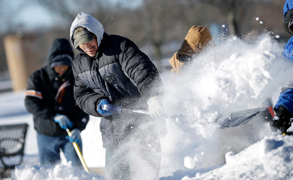 . Workers clear snow Wednesday, Jan. 22, 2014, in Trenton, N.J., after a swirling storm Tuesday left frigid temperatures and more than a foot of snow in some areas.  (AP Photo/Mel Evans)
