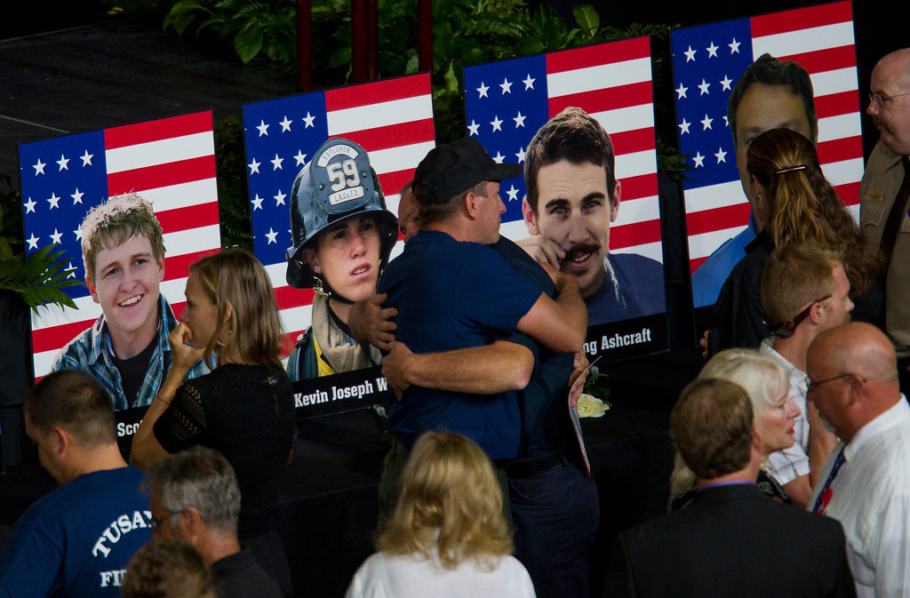 . Photos of some of the 19 fallen firefighters line the front of the stage before a memorial service for the 19 fallen firefighters at Tim\'s Toyota Center in Prescott Valley, Ariz. on Tuesday, July 9, 2013.   Prescott\'s Granite Mountain Hotshots were overrun by smoke and fire while battling a blaze on a ridge in Yarnell, about 80 miles northwest of Phoenix on June 30, 2013.   (AP Photo/The Arizona Republic, Michael Chow, Pool)