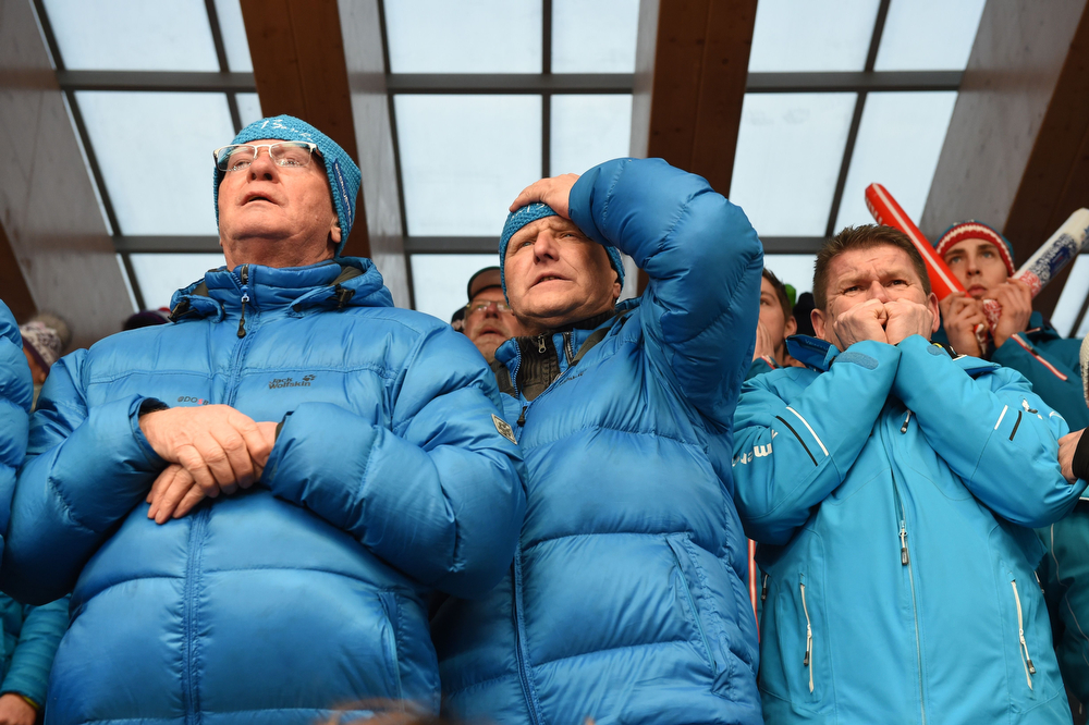 . Fans of Germany\'s Sascha Benecken and Toni Eggert watch as the team races in the Luge Doubles Run 1 at the Sanki Sliding Center during the Sochi Winter Olympics on February 12, 2014.  (LEON NEAL/AFP/Getty Images)