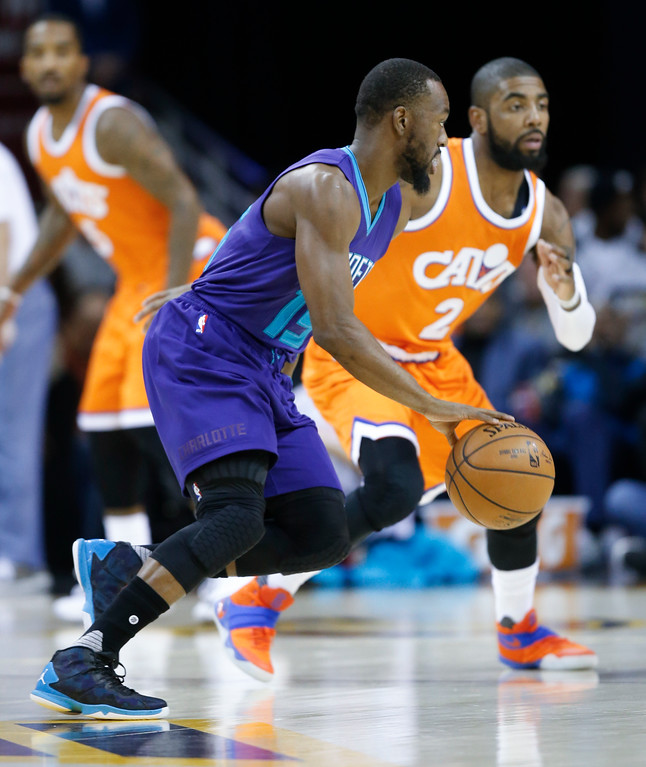 . Charlotte Hornets\' Kemba Walker (15) drives against Cleveland Cavaliers\' Kyrie Irving (2) during the first half of an NBA basketball game Saturday, Dec 10, 2016, in Cleveland. (AP Photo/Ron Schwane)