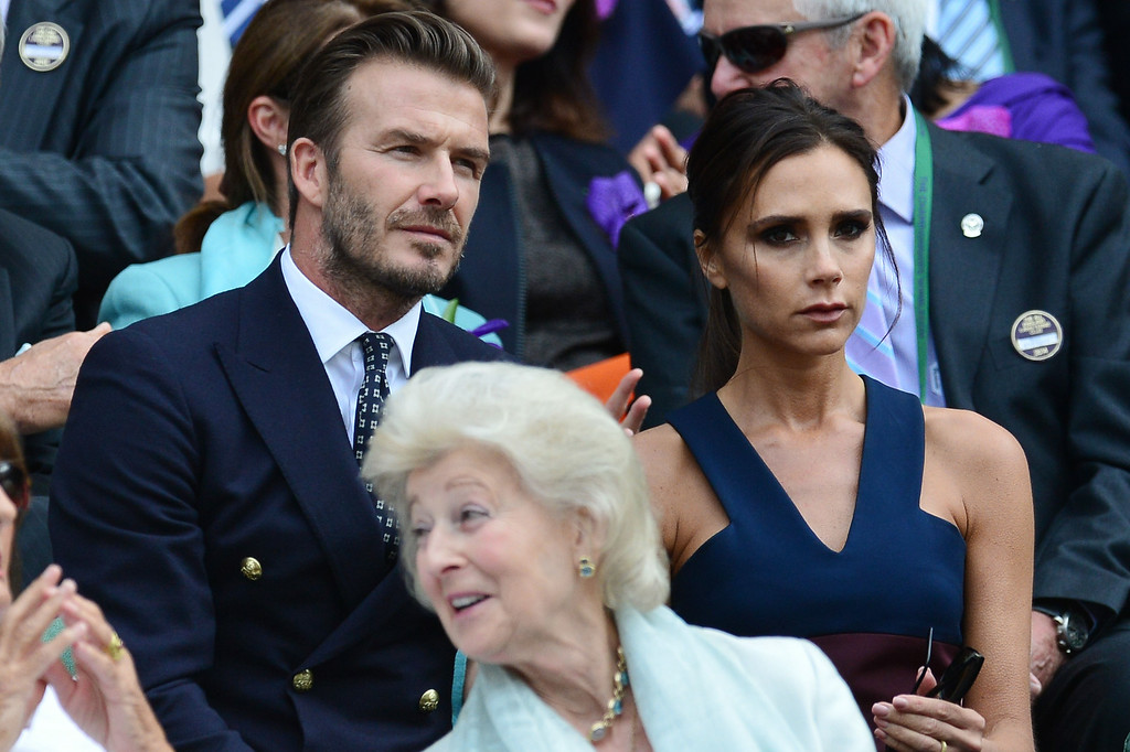 . Former English footballer David Beckham and his wife Victoria sit in the Royal Box on Centre Court before the start of the men\'s singles final match between Serbia\'s Novak Djokovic and Switzerland\'s Roger Federer on day thirteen of the 2014 Wimbledon Championships at The All England Tennis Club in Wimbledon, southwest London, on July 6, 2014.   CARL COURT/AFP/Getty Images
