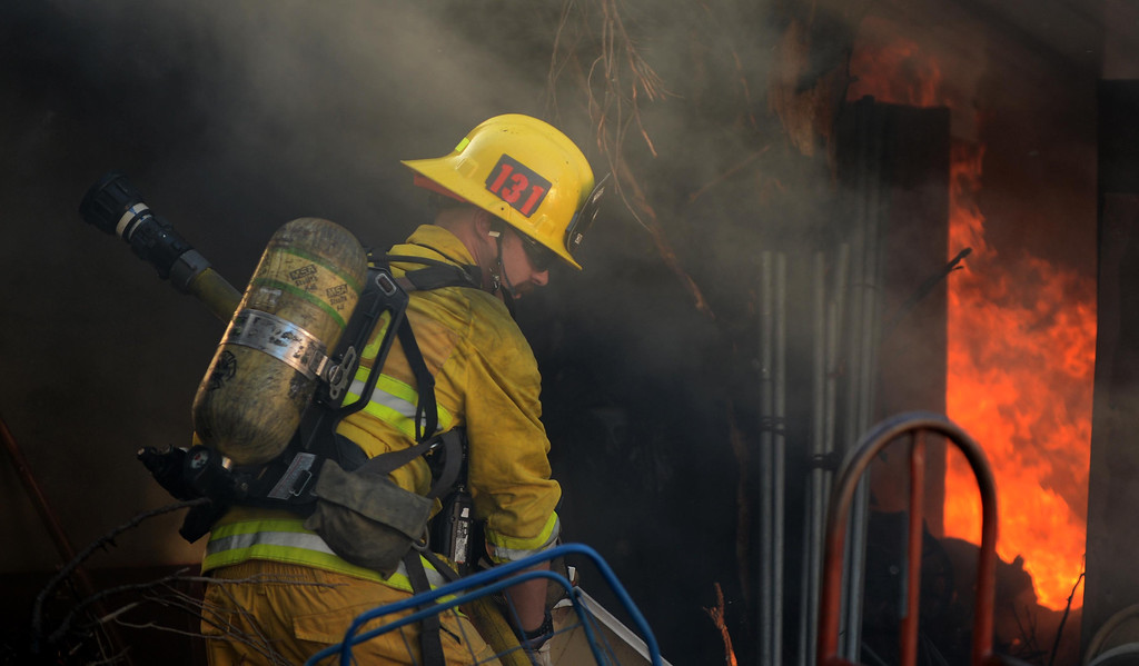 . Firefighters battle a fire that destroyed at least 11 out buildings and 40 vehicles on Tuesday at 5900 Mission Blvd in Jurupa Valley.LaFonzo Carter/ Staff Photographer