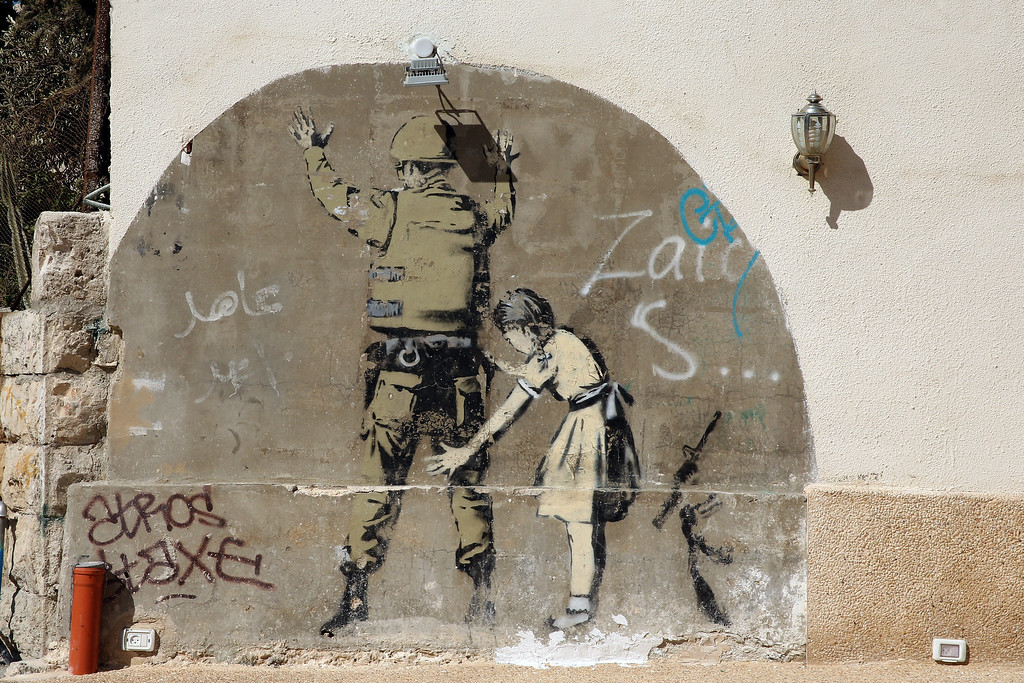 . General views of a Banksy wall painting, on the apartheid wall near Bethlehem on June 16, 2013 in central West Bank.  (Photo by Ian Walton/Getty Images)