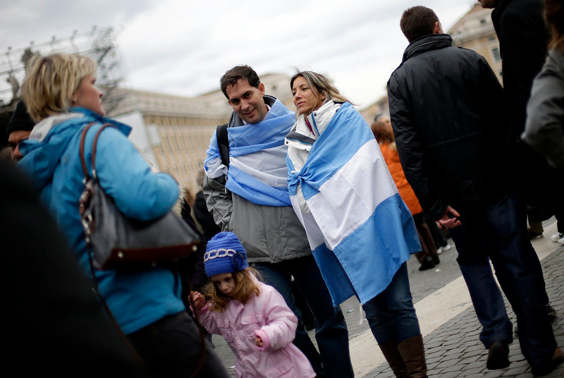 . A couple walks, wrapped in Argentinian national flags, at the end of the Sunday Angelus prayer led by newly elected Pope Francis in St. Peter\'s Square at the Vatican March 17, 2013.      REUTERS/Max Rossi