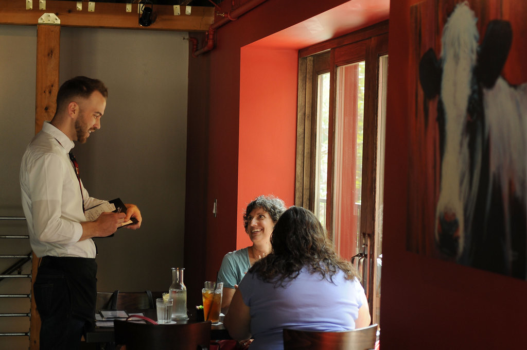 . Michael Posz takes orders from Patty Gordon, center, of Minneapolis and Susan Boinis, of St. Paul at Red Cow on Selby Avenue in St. Paul on Thursday, July 10, 2014.  (Pioneer Press: Scott Takushi)