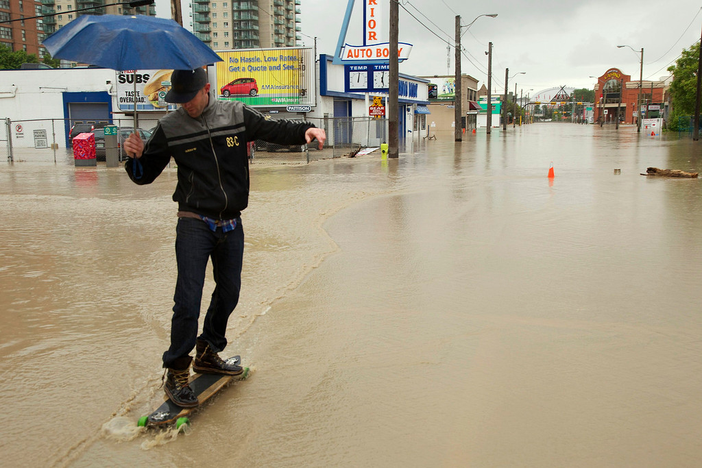 . A man longboards through a flooded downtown street in Calgary, Alberta June 21, 2013.  REUTERS/Melissa Renwick