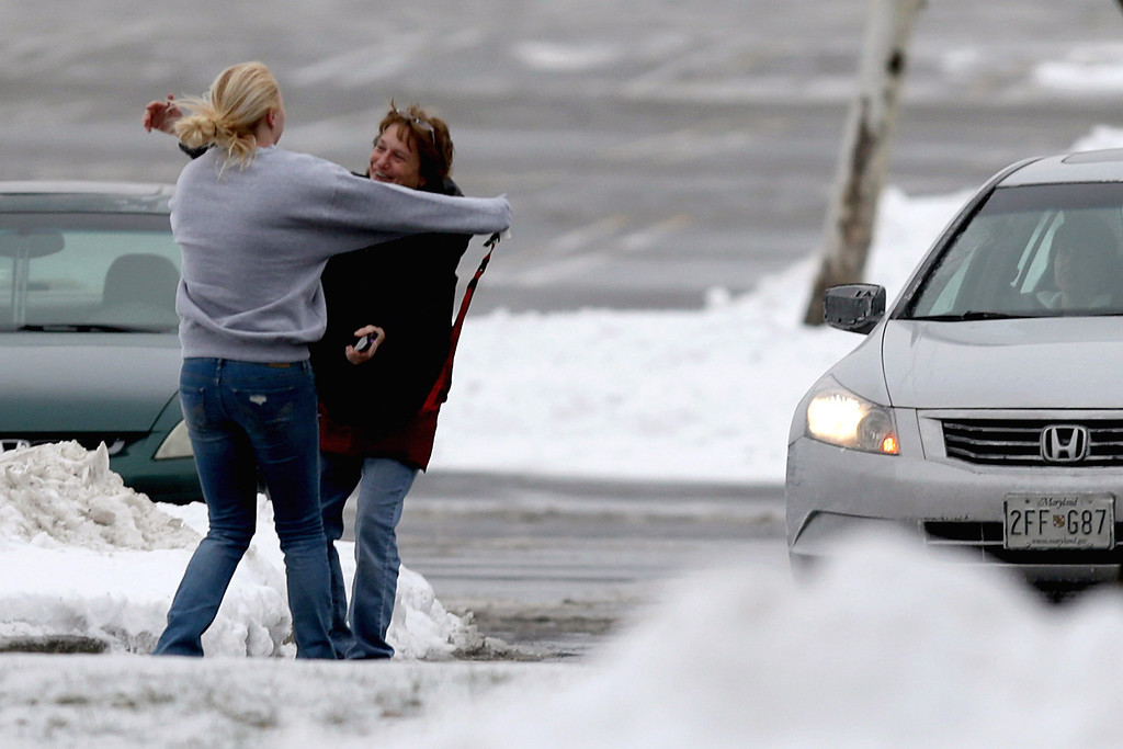 . Two women run to embrace each other outside the Columbia Town Center Mall after three people were killed in a shooting there January 25, 2014 in Columbia, Maryland. Police still do not have a motive for the shooting but believe the shooter has been killed. (Photo by Chip Somodevilla/Getty Images)
