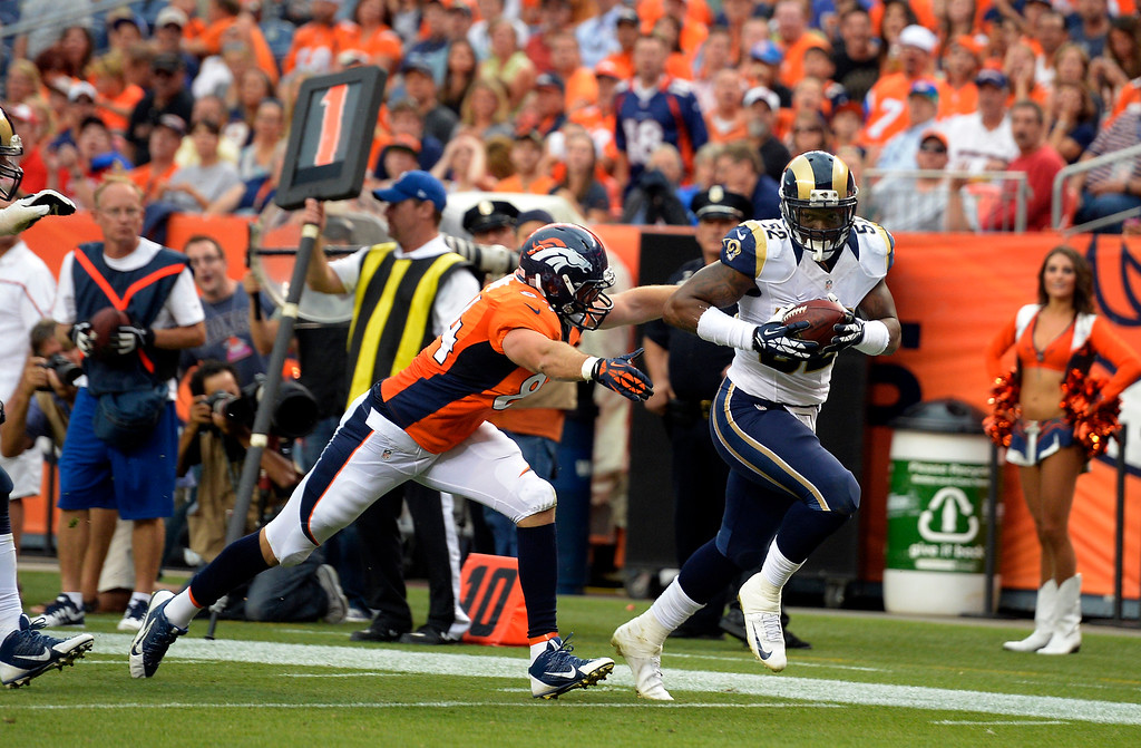. DENVER, CO. - AUGUST 17: St. Louis Rams linebacker Alec Ogletree (52) picks up a fumble and returns it for a touchdown as Denver Broncos tight end Jacob Tamme (84) tries for the tackle during the second quarter August 24, 2013 at Sports Authority Field at Mile High. (Photo By John Leyba/The Denver Post)