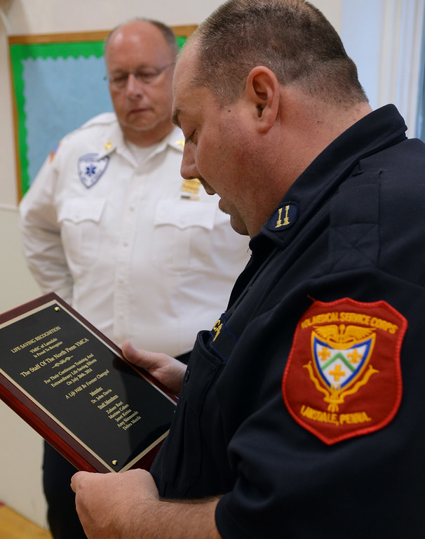 """. Volunteer Medical Service Corps of Lansdale Captain John Hanksworth (R0 and President Tim Duningan present a \""""Life Saving Recognition Award to North Penn YMCA staff for their recent emergency medical response to an incident at the YMCA. Thursday August 21,2014. Photo by Mark C Psoras/The Reporter"""