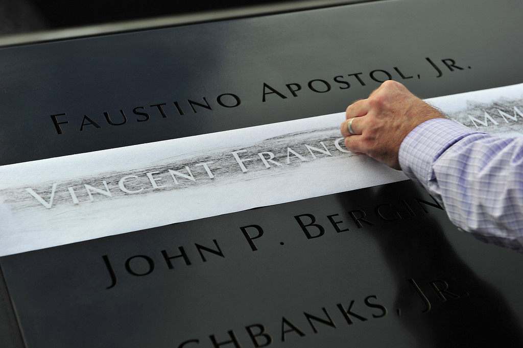 . Ron Joy makes a rubbing of his friend\'s name, New York Fire Department firefighter Capt. Vincent Giammona, at the South reflecting pool of the 9/11 Memorial during ceremonies for the twelfth anniversary of the terrorist attacks on lower Manhattan at the World Trade Center site on September 11, 2013 in New York City. (Photo by Stan Honda-Pool/Getty Images)