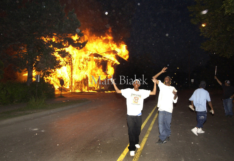 People demonstrate in front of a burning house on Empire Street shortly after dark in Benton Harbor Tuesday night 0n 6/18/2003.  (Photo by Mark Bialek)