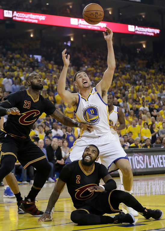 . Golden State Warriors guard Klay Thompson (11) reaches for the ball over Cleveland Cavaliers forward LeBron James (23) and guard Kyrie Irving (2) during the first half of Game 5 of basketball\'s NBA Finals in Oakland, Calif., Monday, June 12, 2017. (AP Photo/Marcio Jose Sanchez)