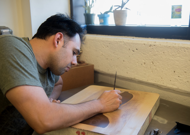 Student George Stockner carves a lithograph for Professor O'Malley's Printmaking course.