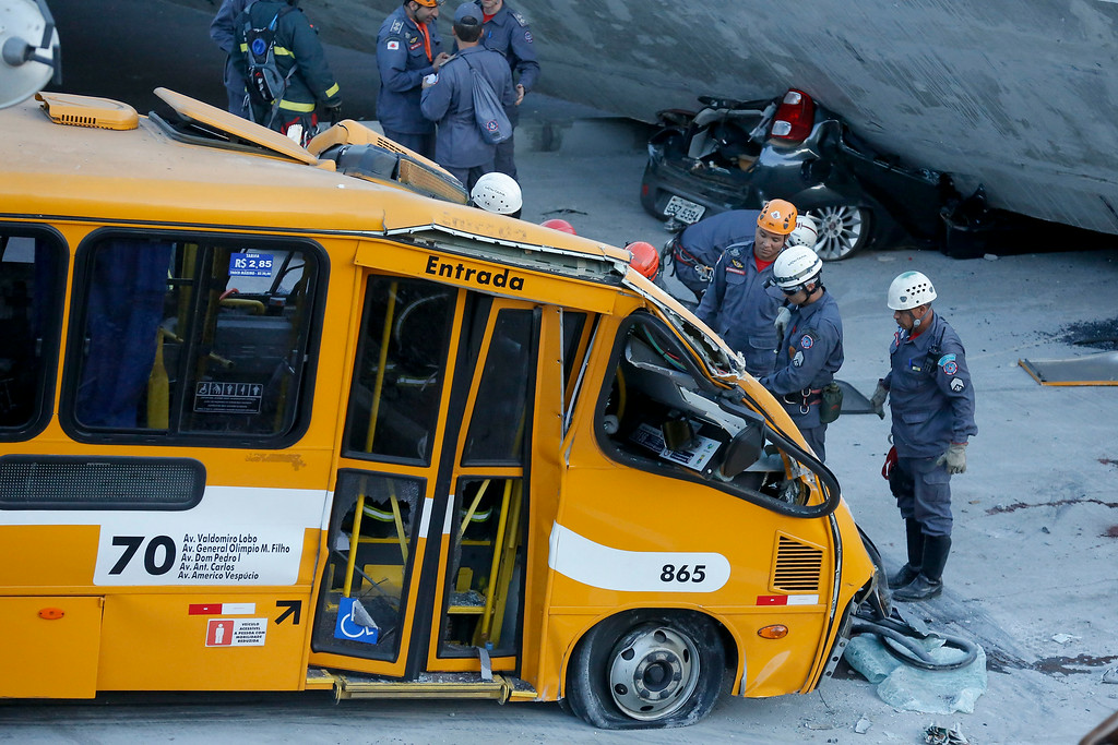 . Fire department personnel work to retrieve a body from a bus after retrieving it from underneath a collapsed bridge in Belo Horizonte, Brazil, Thursday, July 3, 2014. The overpass under construction collapsed Thursday in the Brazilian World Cup host city. The incident took place on a main avenue, the expansion of which was part of the World Cup infrastructure plan but, like most urban mobility projects related to the Cup, was not finished on time for the event. (AP Photo/Victor R. Caivano)