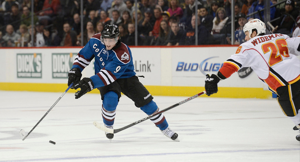 . Matt Duchene (9) of the Colorado Avalanche tries to keep the puck away from Dennis Wideman (26) of the Calgary Flames as he skates towards the blue line during the second period April 8, 2013 at Pepsi Center. (Photo By John Leyba/The Denver Post)