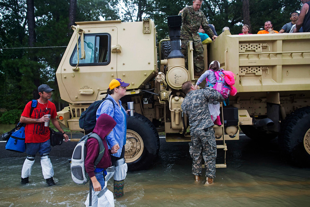 . Kevin Richmond, left, and Barbara Manuel and her two children Elliott, 8, center, and Emily, 5, right, are rescued by members of the Louisiana Army National Guard from rising floodwater near Walker, La., after heavy rains inundated the region, Sunday, Aug. 14, 2016. (AP Photo/Max Becherer)