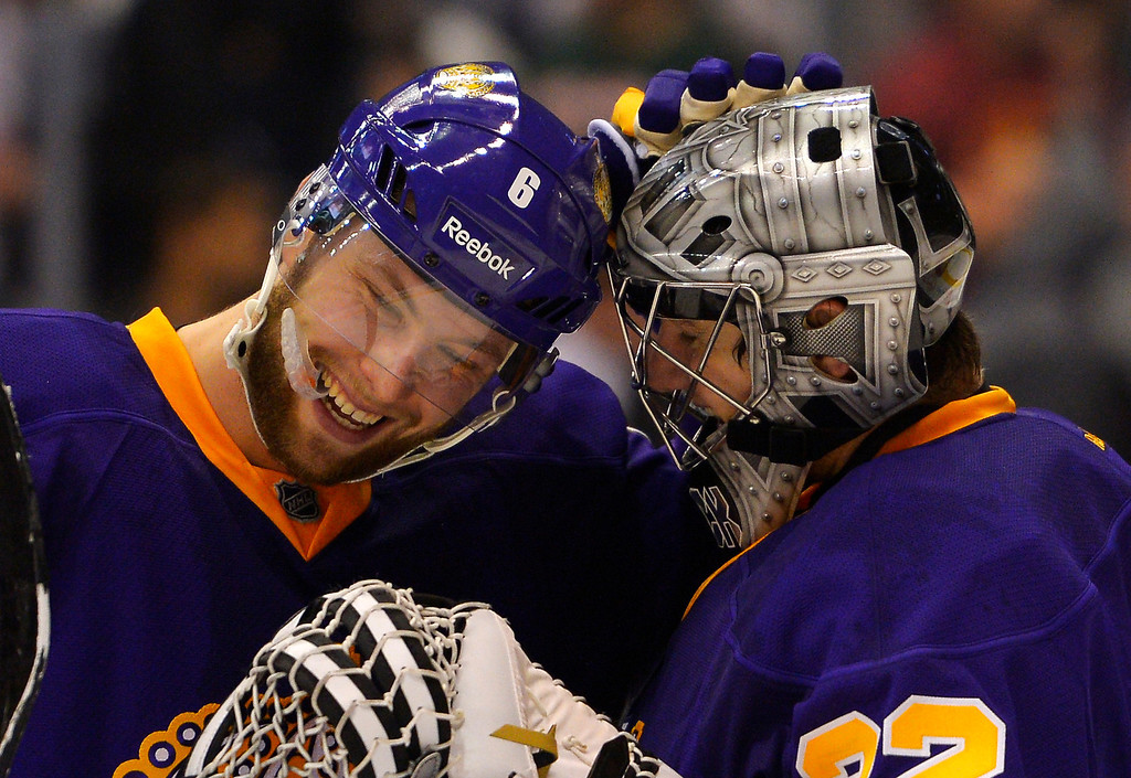 . Los Angeles Kings defenseman Jake Muzzin, left, congratulates goalie Jonathan Quick after their NHL hockey game against the Colorado Avalanche, Saturday, Feb. 23, 2013, in Los Angeles. The Kings won 4-1.  (AP Photo/Mark J. Terrill)