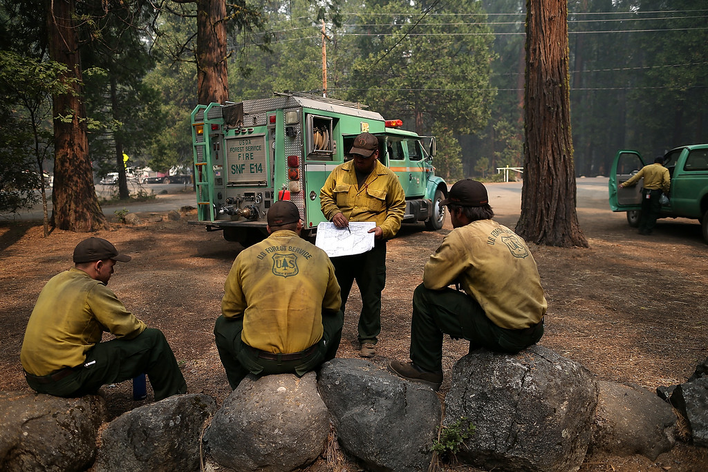 . U.S. Forest Service firefighters take a break from battling the Rim Fire at Camp Mather on August 25, 2013 near Groveland, California.  (Photo by Justin Sullivan/Getty Images)