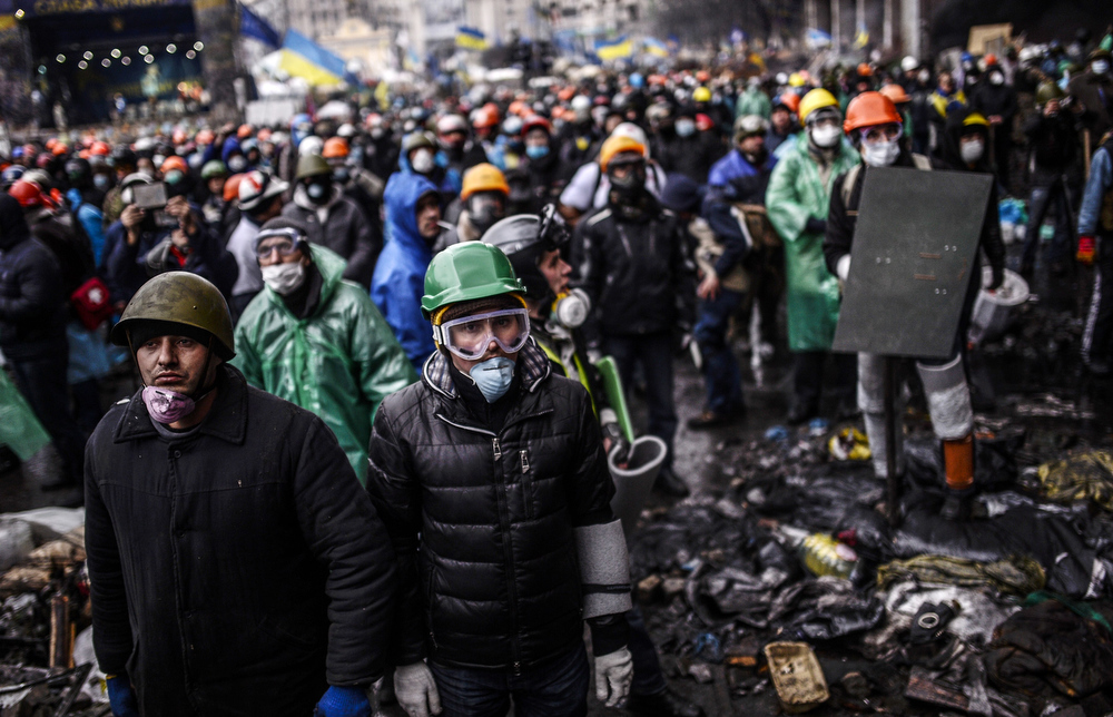 Description of . Protesters stand behind barricades during a face-off against police on February 20, 2014 in Kiev. Ukraine's embattled leader announced a