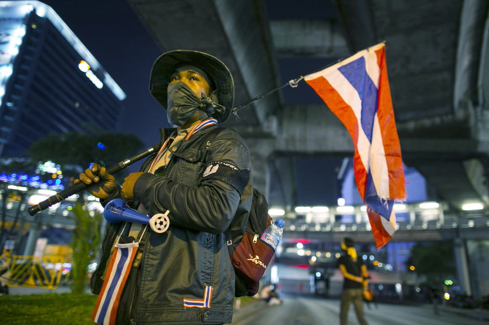 """. A volunteer security guard stands at one of the anti-government People\'s Democratic Reform Committee (PDRC) intersections that was shut down in early evening, blocking a major shopping district on January 12, 2014 in Bangkok, Thailand. There is a fear of more violence and instability as the anti-government protesters move forward with \""""shutdown\"""" of Bangkok by blocking major intersections in the heart of the city during their long running campaign to oust the government of Prime Minister Yingluck Shinawatra. Thailand\'s political crisis has continued for months with elections scheduled for February 2nd. (Photo by Paula Bronstein/Getty Images)"""