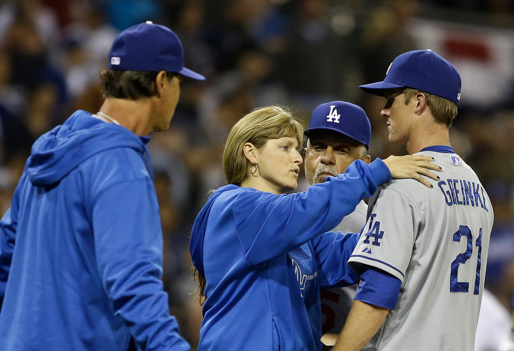 . Los Angeles Dodgers pitcher Zack Greinke is attended to by the team trainer Sue Falsone as manager Don Mattingly, left, and coach Davey Lopes look on during an interlude of a braw that started when Greinke hit San Diego Padres\' Carlos Quentin with a pitch in the sixth inning of baseball game in San Diego, Thursday, April 11, 2013. The battle restarted moments later. (AP Photo/Lenny Ignelzi)