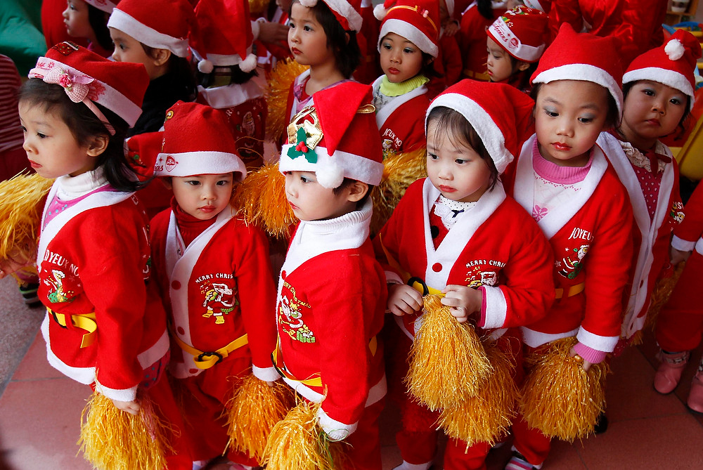 Description of . Children dressed in Santa Claus outfits line up before a Christmas celebration at a kindergarten in Hanoi on December 24, 2012. REUTERS/Kham