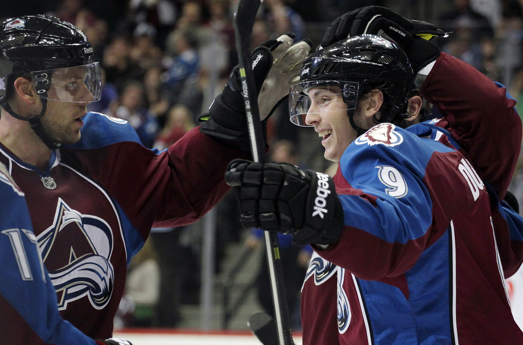 . Colorado Avalanche center Matt Duchene (9) celebrates with Avalanche defenseman Jan Hejda (8), of the Czech Republic, after Duchene\'s goal against the Carolina Hurricanes in the first period of an NHL hockey game in Denver on Friday, Oct. 25, 2013.(AP Photo/Joe Mahoney)