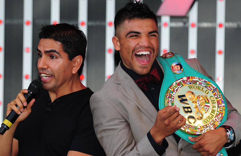 . Boxer Victor Ortiz (R) reacts to fans as radio host Piolin (L) speaks at a pre-fight event at CityWalk in Universal City, California, September 12, 2011.  (ROBYN BECK/AFP/Getty Images)