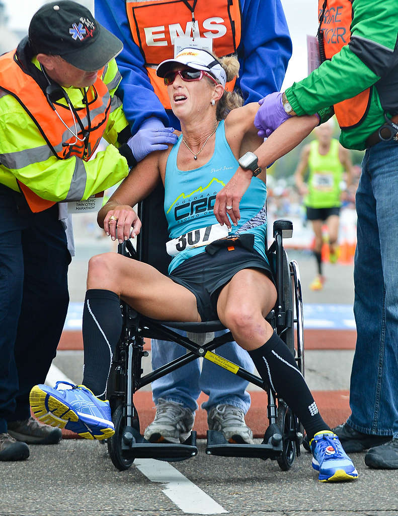 . Joanna Zeiger, 43, of Boulder, Colo., is helped after collapsing on the finish line at the Twin Cities Marathon. (Pioneer Press: Ben Garvin)