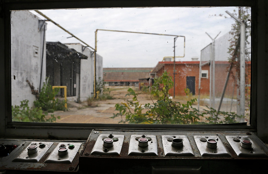 . In this Oct. 23, 2014, photo, buttons that used to open and close many of the gates sit with a view of some of the out buildings at the abandoned Central State Farm prison in Sugar Land, Texas. The unit was closed down three years ago. (AP Photo/Pat Sullivan)