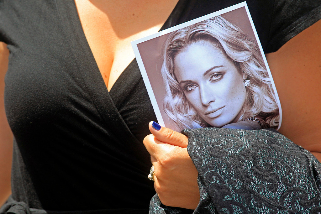 . A woman holds a photo of Reeva Steenkamp, as she leaves her funeral,  in Port Elizabeth, South Africa, Tuesday, Feb. 19, 2013. Olympic athlete Oscar Pistorius is charged with the premeditated murder of Reeva Steenkamp on Valentine\'s Day. The defense lawyer says it was an accidental shooting. (AP Photo/Schalk van Zuydam)