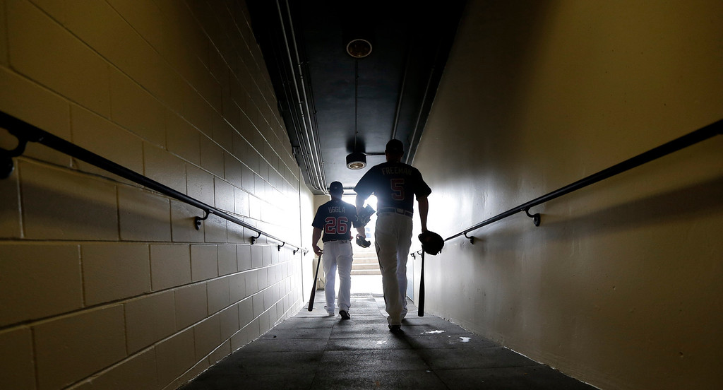 . Atlanta Braves second baseman Dan Uggla (26) and first baseman Freddie Freeman (5) make their way to the field for a spring training baseball workout Wednesday, Feb. 20, 2013, in Kissimmee, Fla. (AP Photo/David J. Phillip)