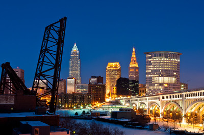 Downtown Cleveland after a winter sunset in 2011, one day after a storm deposited a sheet of ice across the existing blanket of snow, thus causing subtle blues in the sky to be reflected at dusk.  From L-R:  B&O Bridge #463, Key Tower, 200 Public Square, Terminal Tower, Stokes Tower, and the Veterans Memorial Detroit-Superior Bridge.