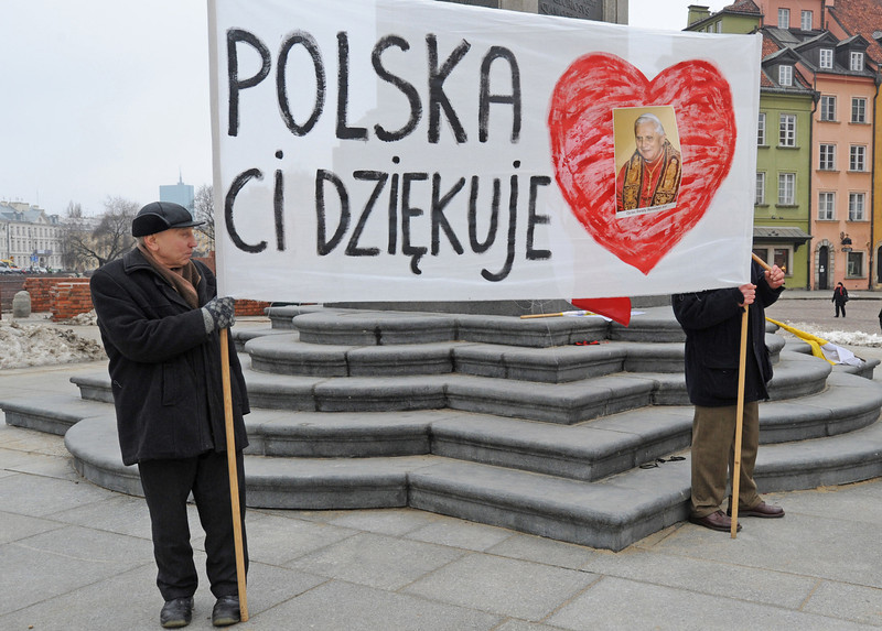 """. Two men stand with a banner reading \""""Poland Thanks You\"""" on the Zamkowy Square in Warsaw, Poland, Thursday, Feb. 28, 2013, on the final day of Pope Benedict XVI\'s papacy. At 8 p.m. Benedict will become the first pontiff in 600 years to resign. (AP Photo/Alik Keplicz)"""