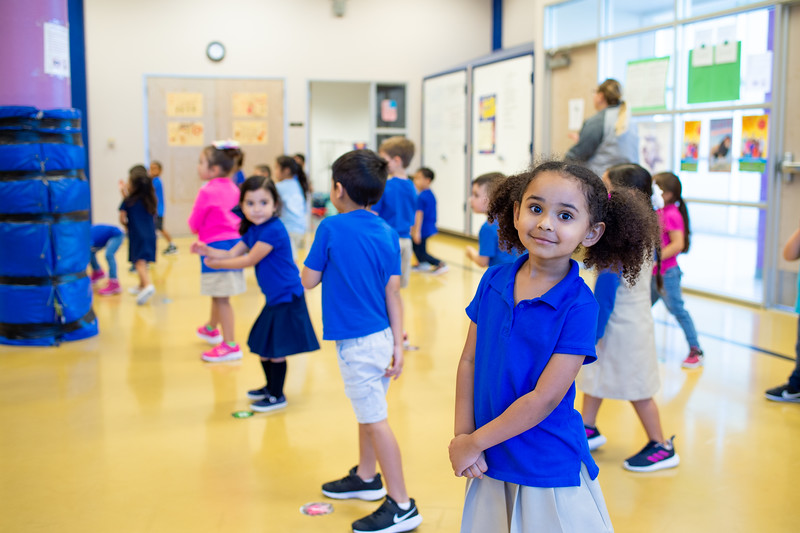 Student Cataleya Clay poses for photo during rec time among classmates, wearing her blue polo for Bluesday Tuesday.