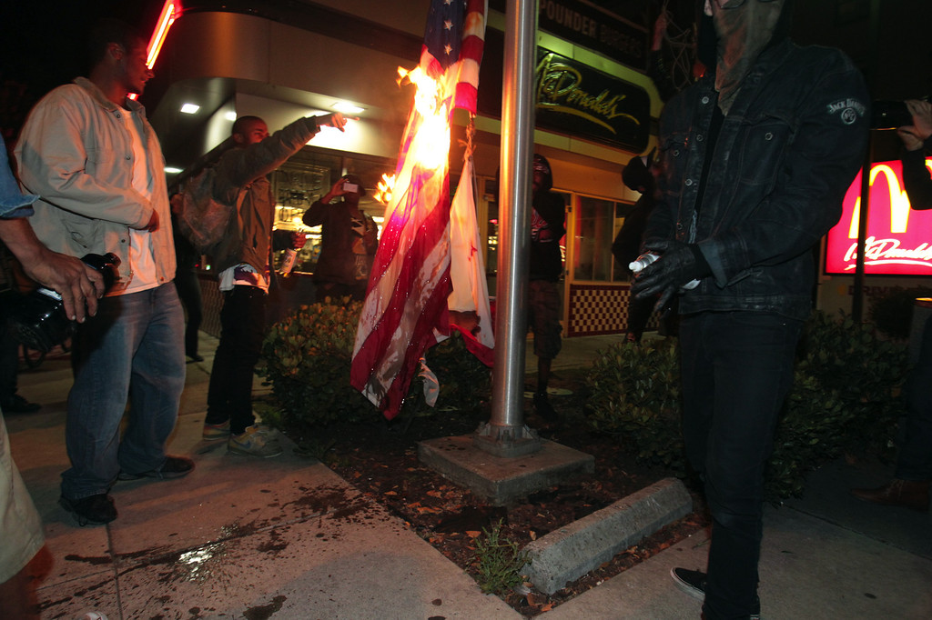 . Marchers burn an American flag outside a fast food restaurant at !4th Street and Jackson during a protest march in Oakland, Calif., early Sunday, July 14, 2013. Protesters marched through the city with some in the group smashing windows, spraying graffiti and setting fires after learning that George Zimmerman had been found not guilty in the shooting of Trayvon Martin. (Anda Chu/Bay Area News Group)