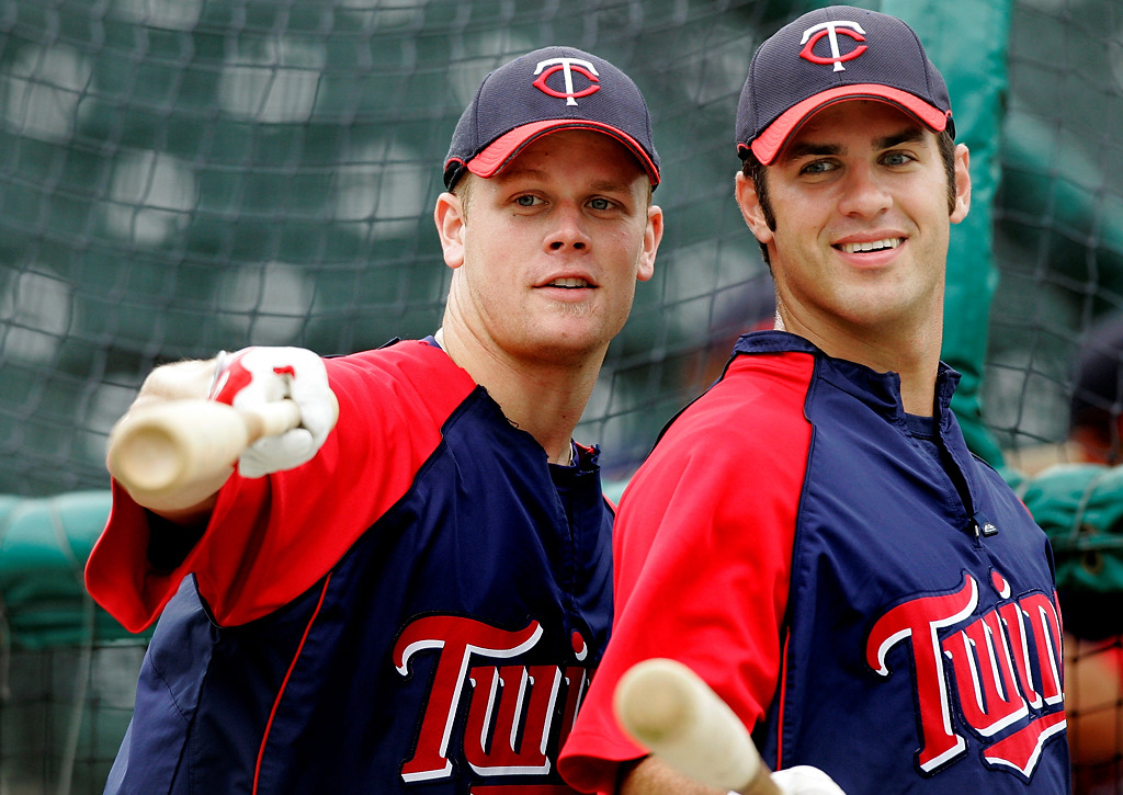 . Minnesota Twins first baseman Justin Morneau, left, and catcher Joe Mauer joke with players in the Cincinnati Reds dugout prior to their spring training game in Fort Myers, Fla., Thursday, March 20, 2008.  (AP Photo/Charles Krupa)
