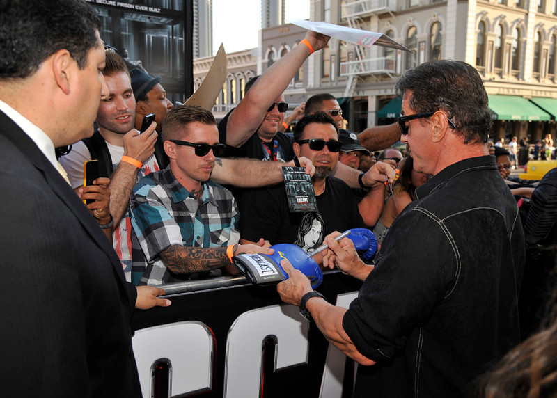 """. Sylvester Stallone signs an autograph as he arrives at the \""""Escape Plan\"""" special screening on Day 2 of Comic-Con International on Thursday, July 18, 2013 in San Diego, Calif. (Photo by Chris Pizzello/Invision/AP)"""