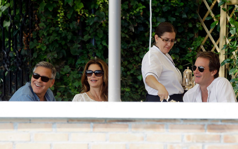 . George Clooney, left, Cindy Crawford and her husband Rande Gerber sit in the garden of the Cipriani hotel in Venice, Italy, Saturday, Sept. 27, 2014. Clooney, 53, and Amal Alamuddin, 36, are expected to get married this weekend in Venice, one of the world\'s most romantic settings. (AP Photo/Andrew Medichini)