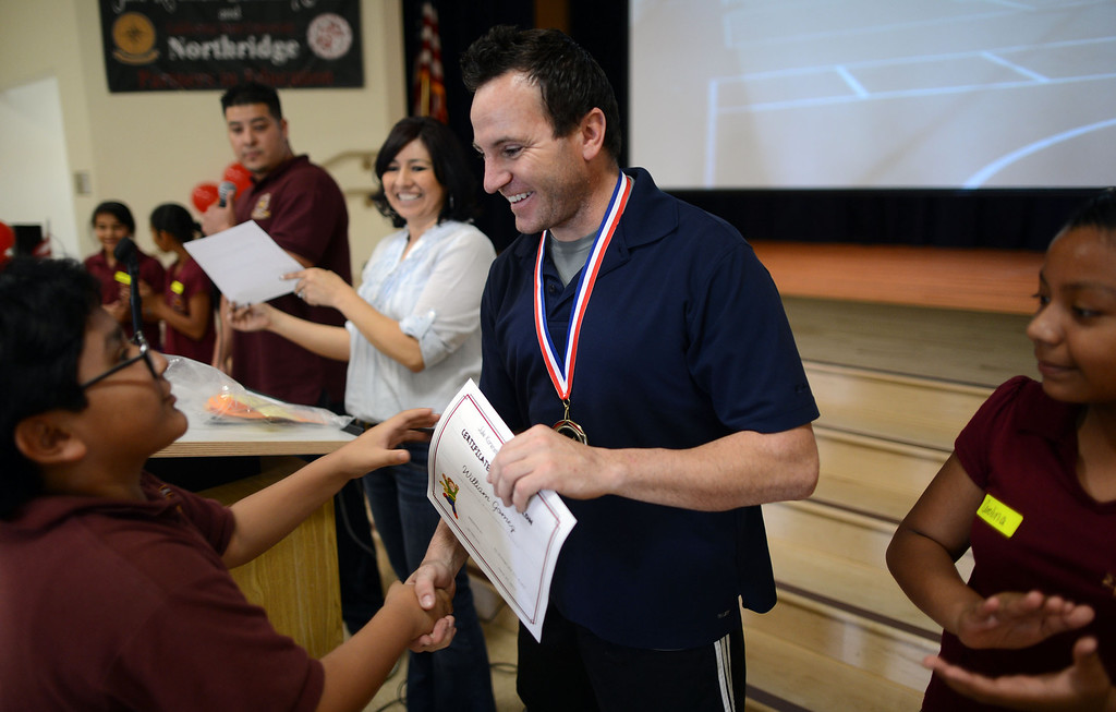 . Paralympian John Siciliano hands out certificates to students at Korenstein Elementary School as part of  Ready, Set, Gold, a public-private partnership with the Southern California Committee for the Olympic Games that is designed to motivate children to set and reach their goals, primarily in health and fitness to help combat childhood obesity and diabetes. (Hans Gutknecht/Staff Photographer)