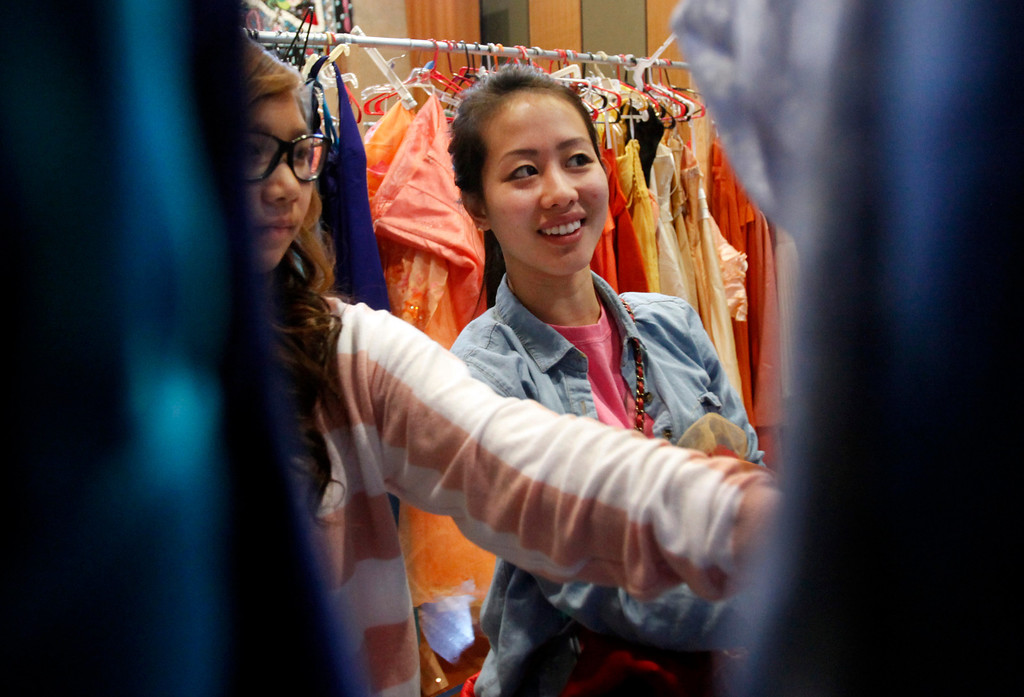 . Linda Tran, right, searches through the racks at Operation Prom Dress, holding its fifth annual event Sunday, March 10, 2013 at Seven Trees Community Center in San Jose, Calif. 800 girls had a chance to pick a prom dress without any worry about the expense. Since 2009, the office of Vice Mayor Madison Nguyen has given out more than 3000 dresses. (Karl Mondon/Staff)