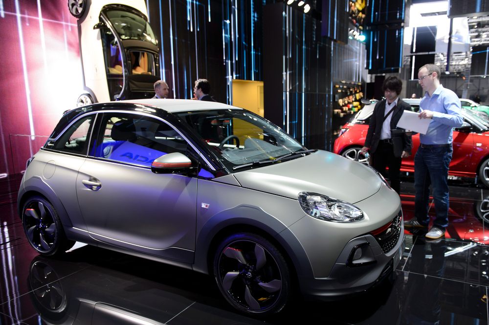 . A journalist inspects the new Opel Adam Rocks  during the press day at the 84.  Geneva International Motor Show in Geneva, Switzerland, Tuesday, March 4, 2014. (AP Photo/Keystone,Martial Trezzini)