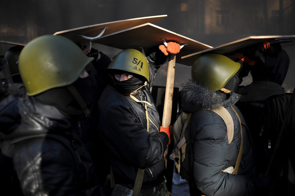 . Anti-government protesters use wooden shields to protect themselves from the bullets fired by the riot police during an anti-government protest in downtown Kiev, Ukraine, 18 February 2014.  EPA/ALEXEY FURMAN